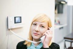 Белокурая женщина отвечает звонку внутренной связи Стоковые Фото