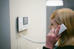 Белокурая женщина отвечает звонку внутренной связи Стоковое Фото