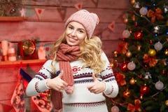 Белокурая женщина одела в уютном пуловере с ее большими пальцами руки вверх Стоковые Изображения RF