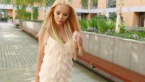 Белокурая женщина представляя в модном платье, внешней съемке видеоматериал