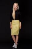 Белокурая женщина при длинные волосы представляя на черной предпосылке Стоковое Фото