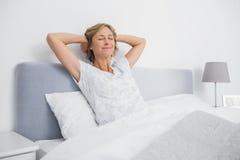 Белокурая женщина протягивая и усмехаясь в кровати Стоковое фото RF