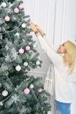 Белокурая женщина развертывая красочно упакованный Новый Год представляет Стоковые Фотографии RF