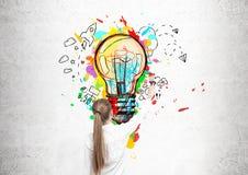 Белокурая женщина рисуя электрическую лампочку Стоковые Фото