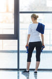 Белокурая женщина стоя и держа гантели в спортзале Стоковые Фотографии RF