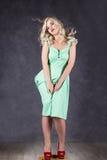 Белокурая женщина с волосами в ветре сексуальная девушка при волосы летания представляя в зеленом платье и красных ботинках Стоковые Изображения