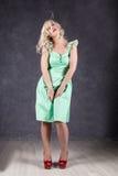 Белокурая женщина с волосами в ветре сексуальная девушка при волосы летания представляя в зеленом платье и красных ботинках Стоковое Фото