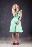 Белокурая женщина с волосами в ветре сексуальная девушка при волосы летания представляя в зеленом платье и красных ботинках Стоковое Изображение