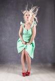 Белокурая женщина с волосами в ветре сексуальная девушка при волосы летания представляя в зеленом платье и красных ботинках Стоковые Фото