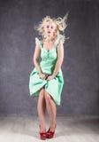 Белокурая женщина с волосами в ветре сексуальная девушка при волосы летания представляя в зеленом платье и красных ботинках Стоковые Изображения RF
