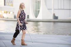 Белокурая женщина с костылями стоковое изображение