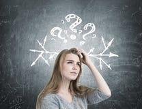 Белокурая женщина царапая голову, вопросы, стрелки Стоковое Изображение