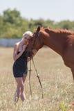 Белокурая женщина штрихуя gelding стоковые изображения rf
