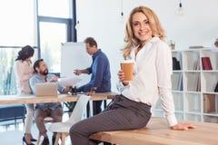 Белокурая коммерсантка сидя на таблице и выпивая кофе пока коллеги работая позади Стоковое фото RF