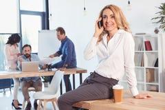 Белокурая коммерсантка сидя на таблице и говоря на smartphone пока коллеги работая позади Стоковая Фотография RF