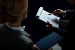 Белокурая коммерсантка смотря контракт бизнесмена подписывая Стоковое Изображение