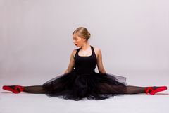 Белокурая красивая девушка в черном платье балетной пачки делая гимнастическое разделение Стоковое Изображение RF