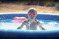 Белокурая маленькая девочка играя в бассейне