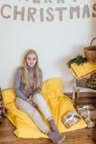 Белокурая маленькая девочка сидя около стены и раскрывая ее настоящие моменты Стоковое фото RF