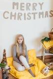 Белокурая маленькая девочка сидя около стены и раскрывая ее настоящие моменты Стоковые Фото