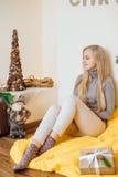 Белокурая маленькая девочка сидя около стены и раскрывая ее настоящие моменты Стоковые Изображения RF