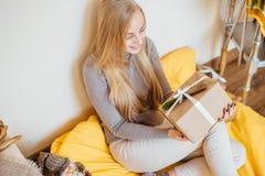 Белокурая маленькая девочка сидя около стены и раскрывая ее настоящие моменты Стоковое Изображение RF
