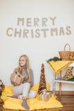 Белокурая маленькая девочка сидя около стены и раскрывая ее настоящие моменты Стоковая Фотография