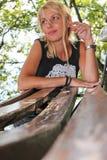 Белокурая склонность женщины на стенде в парке Стоковое фото RF