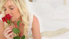 Белокурая с волосами женщина пахнуть розой сток-видео
