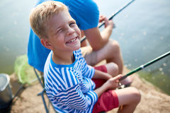 Белокурая усмехаясь рыбная ловля мальчика с папой Стоковое фото RF