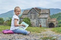 Белокурая школьница рисует мелом на под открытым небом сидеть на том основании Стоковые Фото