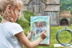 Белокурая школьница рисует мелом outdoors Стоковое Фото