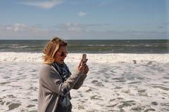 Белокурое женское принимая фото с телефоном океаном Стоковые Фотографии RF