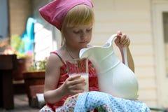 Белокурое питьевое молоко девушки снаружи Стоковые Изображения
