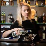 Белокурое питье спирта сервировки девушки Стоковая Фотография