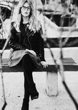 Белокурое gir сидит на стенде, городе лета, черно-белом изображении Стоковая Фотография