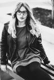 Белокурое gir сидит на стенде, городе лета, черно-белом изображении Стоковые Фотографии RF