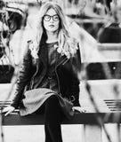 Белокурое gir сидит на стенде, городе лета, черно-белом изображении Стоковые Изображения