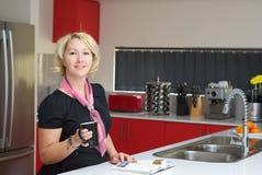 Белокурые женщины в красной кухне Стоковое фото RF