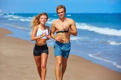 Белокурые молодые пары бежать на пляже в лете Стоковое Фото