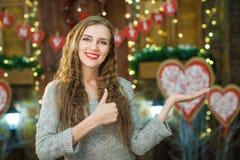 Белокурый показывая большой палец руки вверх и товары выставки на день ` s валентинки Стоковое Изображение