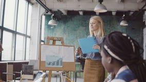 Белокурый руководитель группы женщины представляя новый проект к коллегам Смешанная группа лицо одной расы людей работая на совре акции видеоматериалы