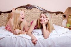 2 белокурых девушки в пижамах лежа на кровати имея полезного время работы Стоковое фото RF