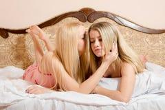 2 белокурых девушки в пижамах лежа на кровати имея полезного время работы Стоковые Изображения RF
