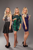 3 белокурых девушки нося платья вечера driknking Мартини Стоковая Фотография