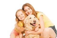 2 белокурых девушки обнимая их золотой Retriever Стоковые Фото