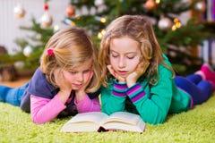 2 белокурых девушки читая книгу перед рождественской елкой Стоковое Изображение RF