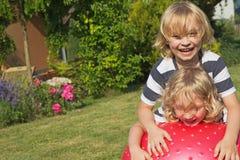 2 белокурых мальчика играют с гимнастическим шариком Стоковое Фото