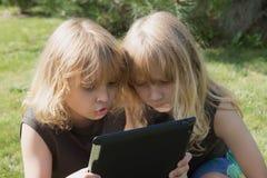 2 белокурых мальчика играют с таблеткой outdoors Стоковые Изображения RF