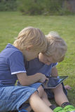 2 белокурых мальчика с ПК таблетки. Стоковое Фото